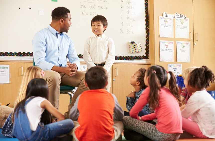 Teacher helps introverted child speak with confidence in front of classroom peers.