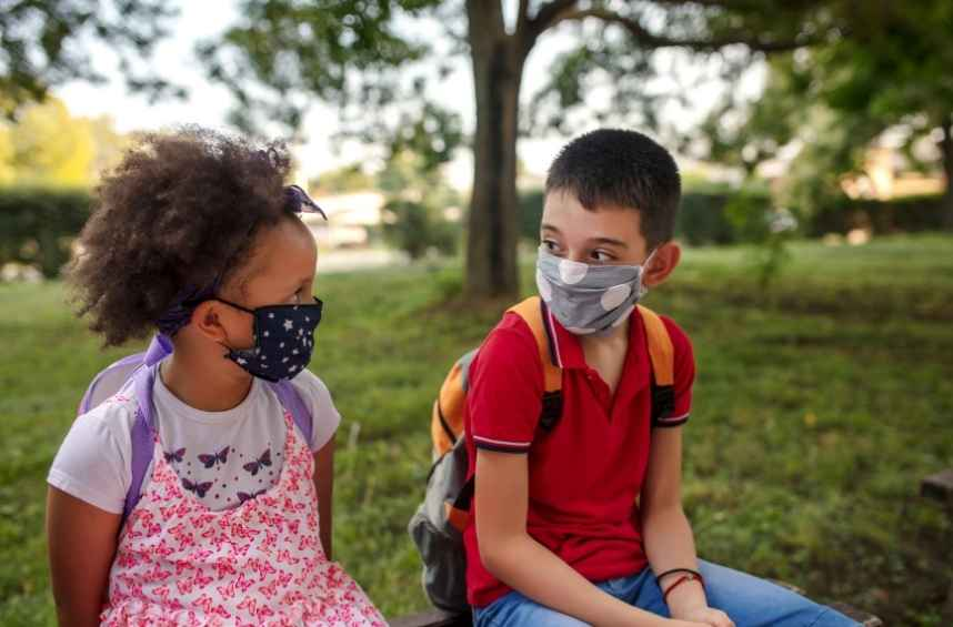 Two children, an introvert and an extrovert, talk with their masks and backpacks on.