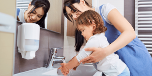 Child washing their hands with the help of a daycare teacher